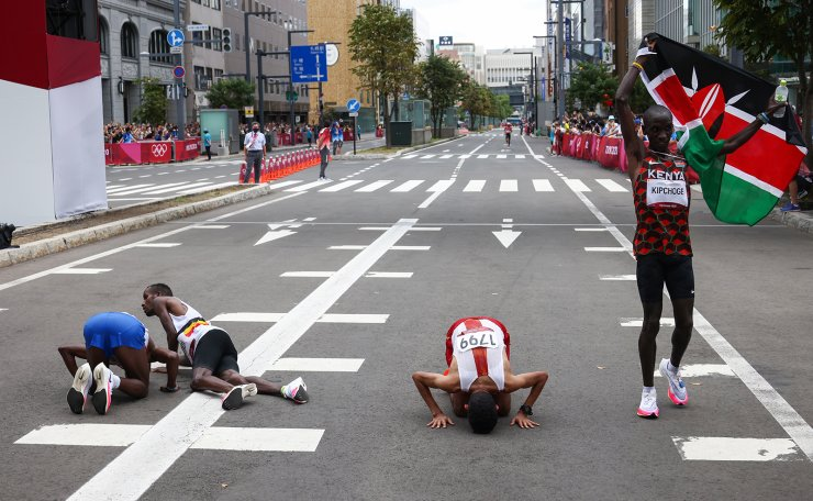 Tokyo 2020 Olympics - Athletics - Men's Marathon - Sapporo Odori Park, Sapporo, Japan - August 8, 2021. Eliud Kipchoge of Kenya holds the flag of Kenya and celebrates after winning gold as Abdi Nageeye of the Netherlands celebrates after winning silver, Bashir Abdi of Belgium celebrates after winning bronze and Ayad Lamdassem of Spain reacts after competing. REUTERS