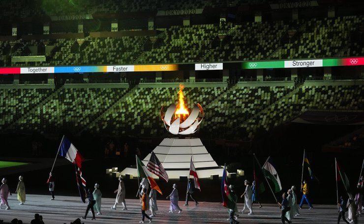 The Olympic flame burns as athletes and volunteers carry flags during the closing ceremony in the Olympic Stadium at the 2020 Summer Olympics, Sunday, Aug. 8, 2021, in Tokyo, Japan. AP