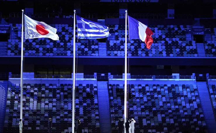 Anne Hidalgo, Mayor of Paris, center, stands with International Olympic Committee's President Thomas Bach, second left, as they raise up the flag of France during the closing ceremony in the Olympic Stadium at the 2020 Summer Olympics, Sunday, Aug. 8, 2021, in Tokyo, Japan. AP