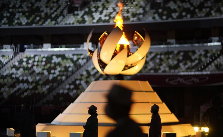 Volunteers stand as International Olympic Committee's President Thomas Bach gives a speech during the closing ceremony in the Olympic Stadium at the 2020 Summer Olympics, Sunday, Aug. 8, 2021, in Tokyo, Japan. AP