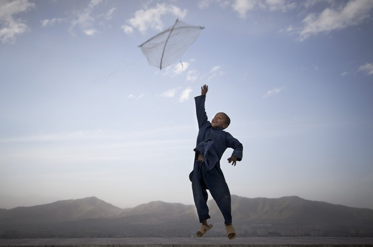 In this May 13, 2013 file photo, a boy flies his kite on a hill overlooking Kabul, Afghanistan. Kite flying was banned during the Taliban regime. AP