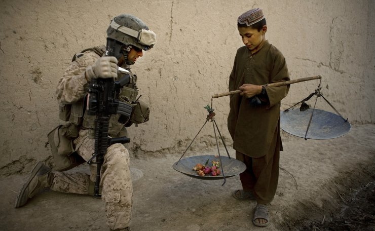 In this Wednesday, Nov. 3, 2010 file photo, First Sgt. Yomen English, of Brookland, Ark., with India company, 3rd Battalion 5th Marines, First Marine Division, talks to an boy during a patrol, in Sangin, Afghanistan. AP