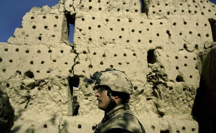 In this Wednesday, Nov. 22, 2006 file photo, a Canadian soldier, and a soldier from the Afghan National Army, behind wall, walk along a destroyed grape drying silo at the Canadian base near the town of Zhari in the Kandahar province of Afghanistan. The holes in the wall are for mounting sticks for drying grapes. AP
