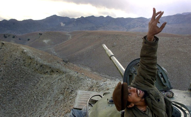 In this Monday, Dec. 10, 2001 file photo, an Afghan anti-Taliban fighter pops up from his tank to spot a U.S. warplane bombing al-Qaida fighters in the White Mountains of Tora Bora in Afghanistan. Anti-Taliban forces and U.S. warplanes continued to hit the Tora Bora mountains and the al-Qaida fighters occupying the area. AP