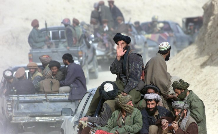 In this Saturday Nov. 24, 2001 file photo, a column of Taliban fighters go through the front line in the village of Amirabad, northern Afghanistan, as hundreds of Taliban defected to the northern alliance, paving the way for the fall of Kunduz where several thousand foreign fighters are thought to remain. AP
