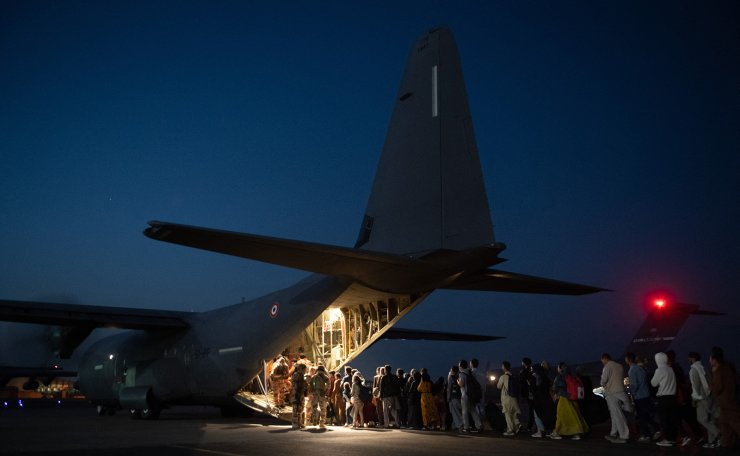 This handout photo taken and released by the French Etat-major des Armees on August 26, 2021 shows people boarding a French military transport aircraft at the airport in Kabul, to fly to the air base of Al Dhafra, near Abu Dhabi, and then to Roissy Charles-de-Gaulle airport, north of Paris, as part of the operation 'Apagan'. AFP