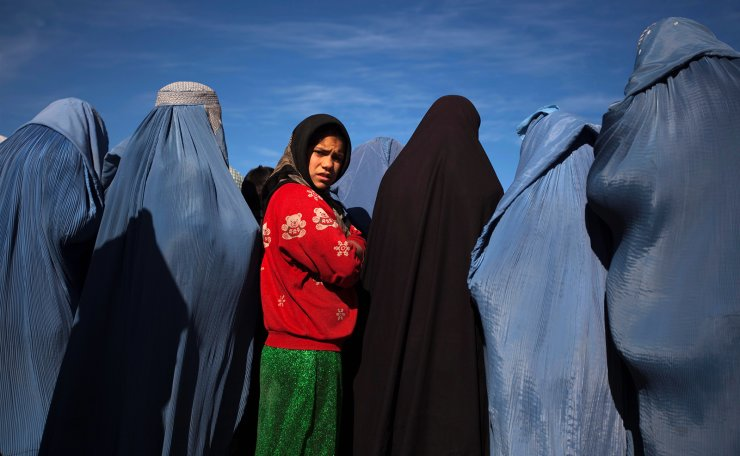 An Afghan girl stands among widows clad in burqas during a cash for work project by humanitarian organisation CARE International in Kabul, Afghanistan January 6, 2010. REUTERS