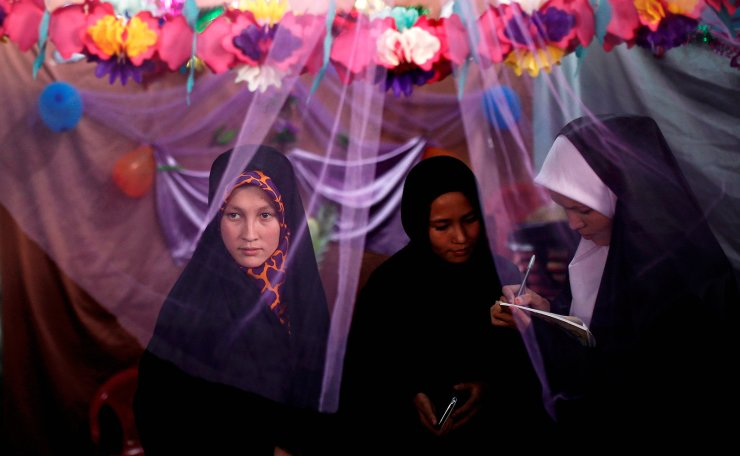 Afghan women stand at a kiosk during the inauguration of 'Spring of Holy Quran' exhibition during the month of Ramadan, in Kabul, Afghanistan June 25, 2015. REUTERS
