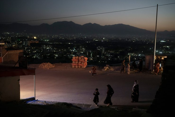 Afghans walk on a road overlooking Kabul, Afghanistan, Tuesday, Sept. 14, 2021. The United Nations drummed up more than $1.2 billion in emergency pledges Monday for helping 11 million Afghans facing an escalating humanitarian crisis in their homeland and millions more elsewhere in the region as the U.N. human rights chief voiced concerns about the Taliban's first steps in establishing power in the beleaguered and impoverished country. AP