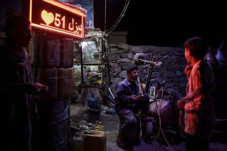 A tire repairman chats with boys as he waits for customers on the side of a road in Kabul, Afghanistan, Tuesday, Sept. 14, 2021. AP