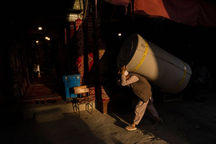 An Afghan labourer carries a roll of foam at a market in Kabul's old city, Afghanistan, Tuesday, Sept. 14, 2021. AP