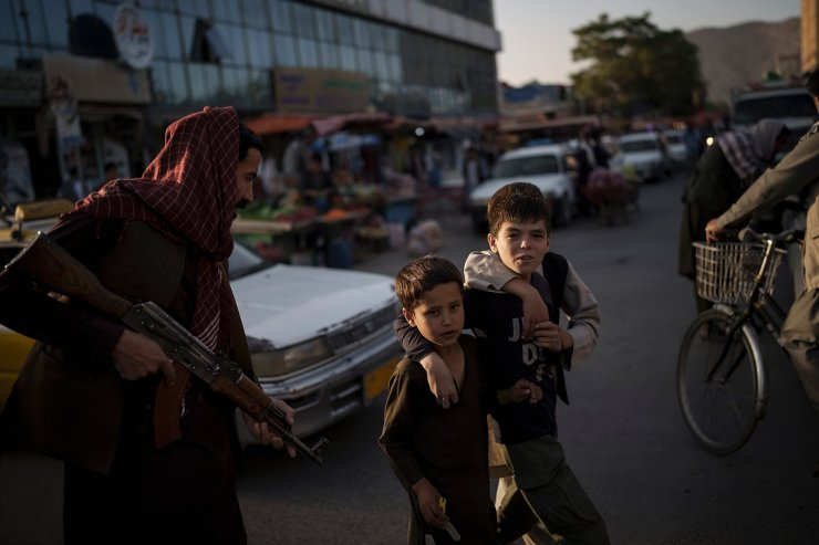 Afghan boys walk past a Taliban fighter as they cross a street in Kabul, Afghanistan, Tuesday, Sept. 14, 2021. AP