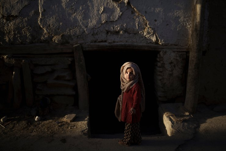 A young afghan girl looks at the camera as she plays outside her house in Kabul, Afghanistan, Wednesday, Sept. 15, 2021. AP
