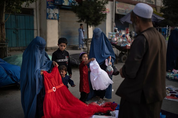 Afghan women and a girl shop for dresses at a local market in Kabul, Afghanistan, Friday, Sept. 10, 2021. AP