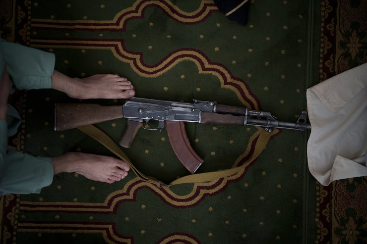 A Taliban fighter lays his AK-47 rifle down during Friday prayers at a Mosque in Kabul, Afghanistan, Friday, Sept. 10, 2021. AP