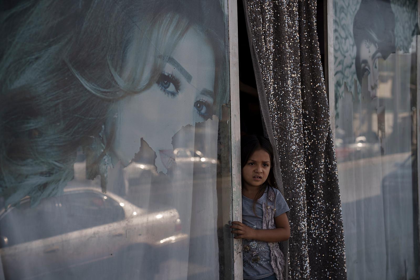 An Afghan girl looks out from a beauty salon in Kabul, Afghanistan, Thursday, Sept. 16, 2021. AP