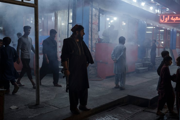 A Taliban fighter stands in the corner of a busy street at night in Kabul, Afghanistan, Friday, Sept. 17, 2021. AP