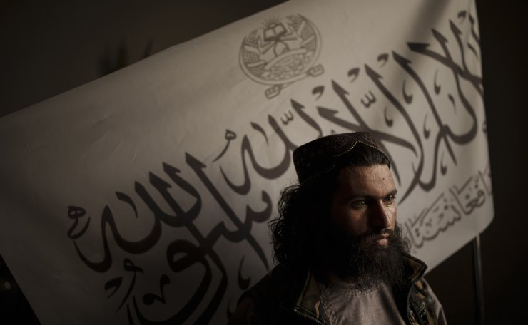 Taliban district police chief Shirullah Badri stands in front of a Taliban flag during an interview at his office in Kabul, Afghanistan, Monday, Sept. 20, 2021. AP