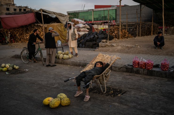 An Afghan boy sits on a wheelbarrow as he waits for customers at a street fruit and vegetable market in Kabul, Afghanistan, Wednesday, Sept. 22, 2021. AP