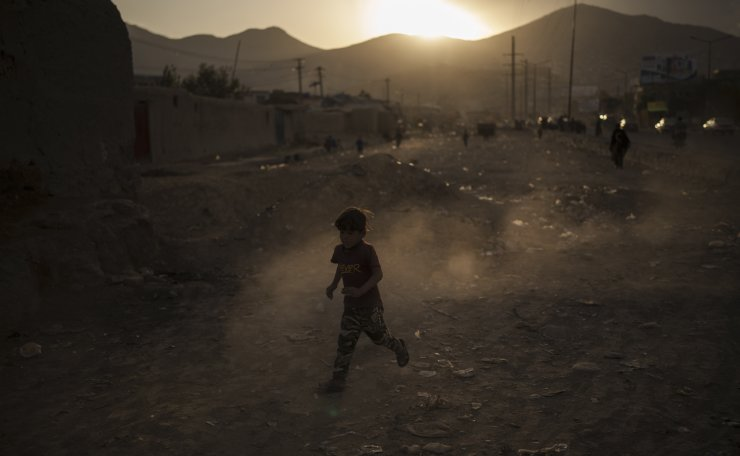 An Afghan boy plays on the side of a road as the sun sets in Kabul, Afghanistan, Wednesday, Sept. 22, 2021. AP