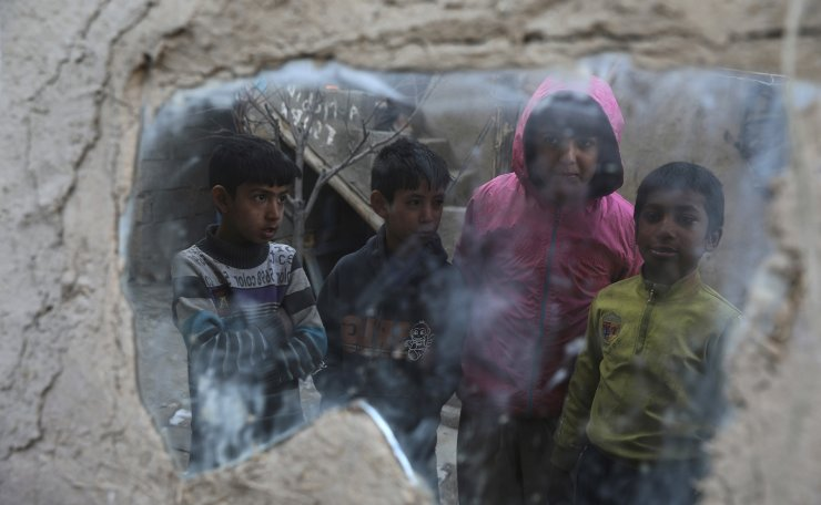 Internally displaced boys are reflected in a mirror inside their temporary home in the city of Kabul, Afghanistan, Wednesday, Dec. 30, 2020. Save the Children has warned that more than 300,000 Afghan children face freezing winter conditions that could lead to illness, in the worst cases death, without proper winter clothing and heating. AP