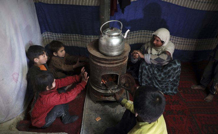 Internally displaced children sit around a stove to keep warm in a temporary shelter in the city of Kabul, Afghanistan, Wednesday, Dec. 30, 2020. AP