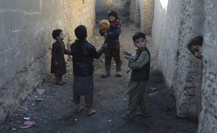 Internally displaced boys play with a ball outside their temporary home in the city of Kabul, Afghanistan, Wednesday, Dec. 30, 2020. AP