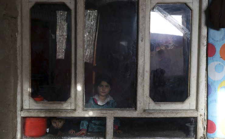 An internally displaced sister and brother pose for a photograph inside their temporary home in the city of Kabul, Afghanistan, Wednesday, Dec. 30, 2020. AP