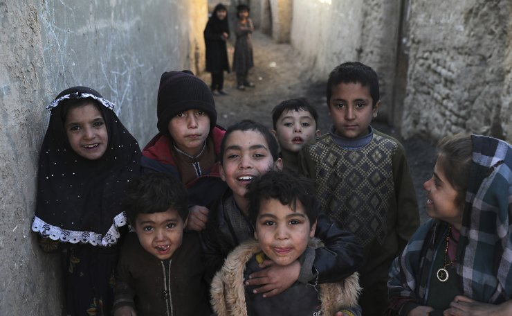 Internally displaced children pose for a photograph outside their temporary home in the city of Kabul, Afghanistan, Wednesday, Dec. 30, 2020. AP