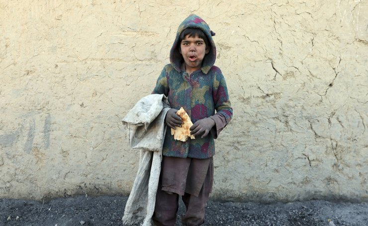 An internally displaced boy poses for a photograph outside his temporary home in the city of Kabul, Afghanistan, Wednesday, Dec. 30, 2020. AP