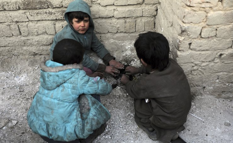 Internally displaced boys warm themselves near a fire outside their temporary home in the city of Kabul, Afghanistan, Wednesday, Dec. 30, 2020. AP
