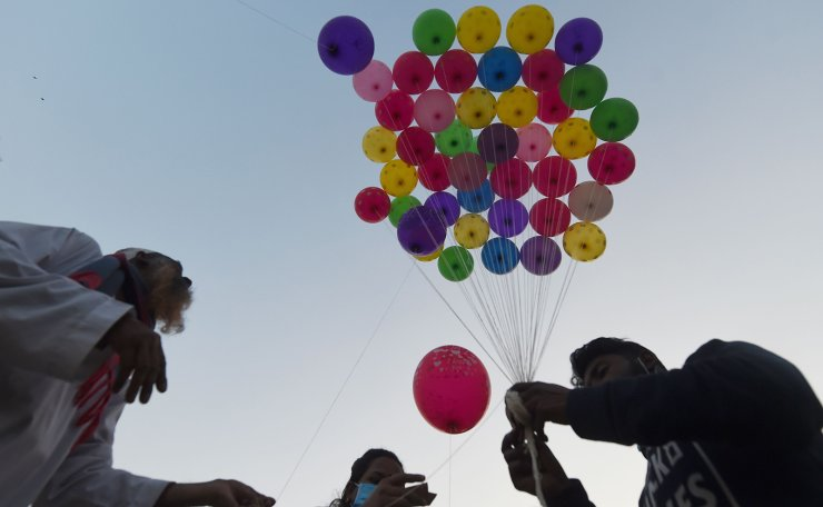 A family buy balloons for their children from a vendor at a park in Dhaka on January 2, 2021. AFP