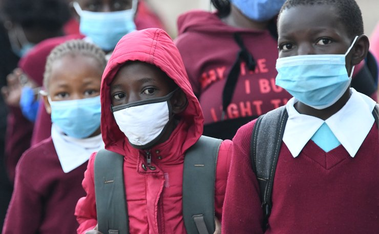 Kenyan school children wear face masks while walking to school as they resume in-class learning after a nine-month disruption caused by the COVID-19 coronavirus pandemic, in Nairobi on January 4, 2021. AFP