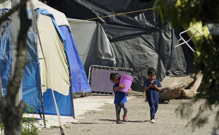 Children walk through a camp of asylum seekers stuck at America's doorstep, in Matamoros, Mexico, Wednesday, Nov. 18, 2020. Led by U.S. military veterans, Global Response Management is staffed by volunteers primarily from the U.S. and paid asylum seekers who were medical professionals in their homelands. The group has treated thousands of migrants over the past year at two clinics in Matamoros, including one inside the camp. AP