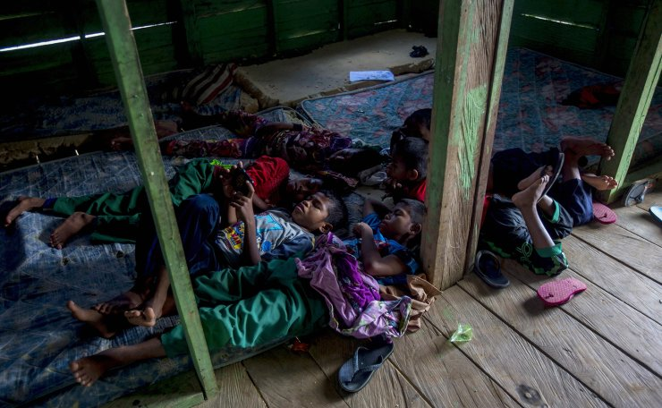 Students of a boarding school rest in their dormitory in North Kalimantan, Indonesia, on Tuesday, April 9, 2019. Some palm oil workers who work illegally in Malaysia send their children to the school in this transit town because they have no access to education in Malaysia due to their parents' employment status. AP