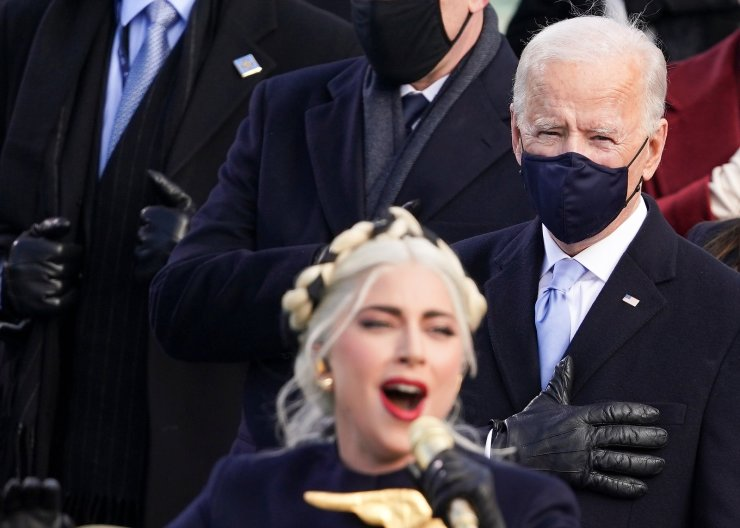 U.S. President-elect Joe Biden stands as Lady Gaga sings the National Anthem during the inauguration of Joe Biden as the 46th President of the United States on the West Front of the U.S. Capitol in Washington, U.S., January 20, 2021. REUTERS