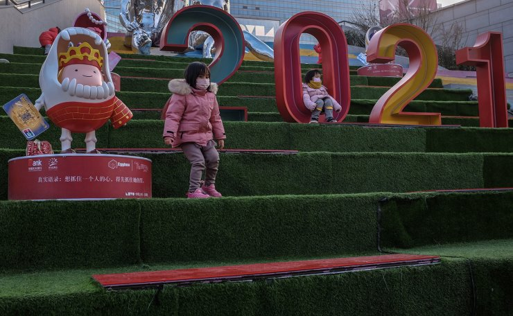 Children play near a 2021 decoration outside a shopping complex during the 2021 New Year holidays amid COVID-19 coronavirus, in Beijing, China, 02 January 2021. EPA