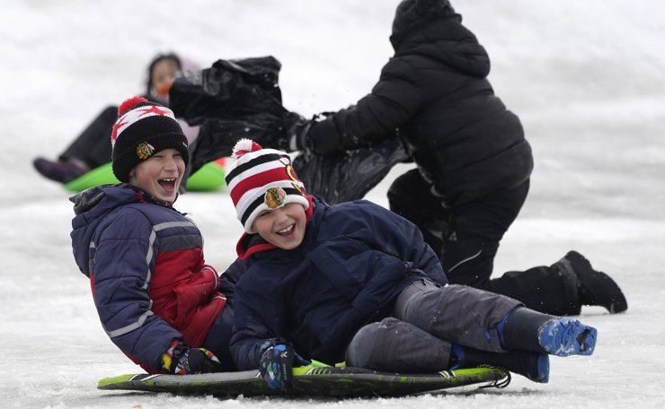 Children enjoy sledding at the Woodland Trails Park Sled Hill in Prospect Heights, Ill., Saturday, Jan. 2, 2021. AP