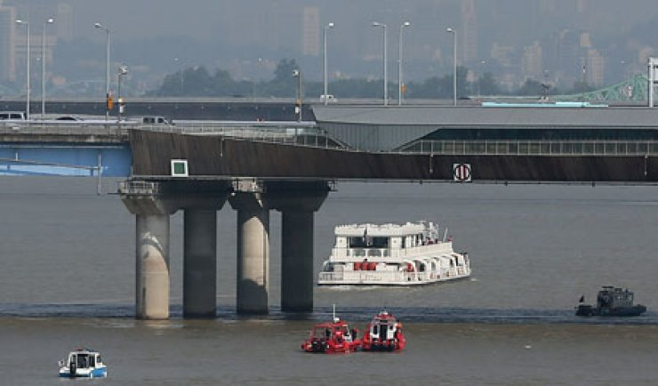Rescue boats from Seoul Metropolitan Fire and Disaster Headquarters search for the body of male rights activist Sung Jae-gi under the Mapo Bridge on the Han River in this photo taken on Friday. Sung jumped off the bridge ostensibly as a way to raise funds for his advocacy group. Police and rescue agents have searched for his body for three days, but failed to find it as of Sunday night. / Yonhap