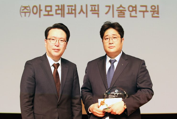 AmorePacific cell science team researcher Kim Hyoung-june, right, poses after receiving the grand prize of the 2017 Dongam Cosmetics Scientist Awards from Beautynury CEO Hahm Sung-won, left, at the Seoul National University of Technology, Friday. / Courtesy of AmorePacific