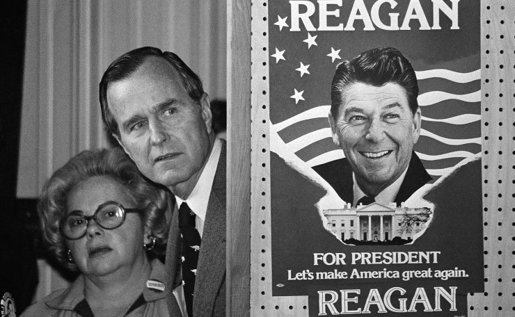 FILE - In this March 4, 1980 file photo, George H.W. Bush and an unidentified woman peek around a partition with a poster of Ronald Reagan, one of his opponents for the Republican party presidential nomination, before he speaks in Columbia, S.C. AP