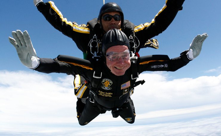 Former U.S. President George H.W. Bush (bottom) celebrates his 85th birthday by jumping with the Army's Golden Knight parachute team in a tandem jump with SFC Michael Elliott in Kennebunkport, Maine in this file handout photo released June 12, 2009. Reuters
