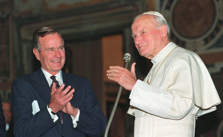 FILE PHOTO: U.S. President George H.W. Bush applauds Pope John Paul II after a welcoming ceremony prior to their audience at the Vatican November 8, 1991. Reuters