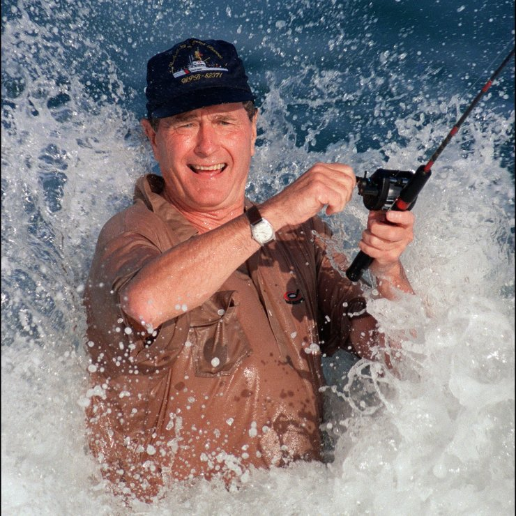 In this file photo taken on November 14, 1988 President elect George Bush is smashed by a wave 14 November 1988 while fishing in back of the home of William Farish in Florida. AFP