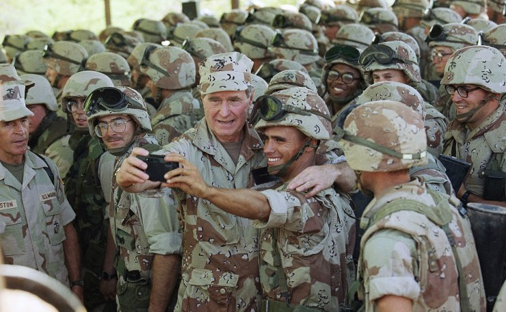 FILE - In this Jan. 1, 1993, file photo, U.S. President George H.W. Bush holds a camera at arm's length for a selfie with Marines at Baidoa's airport in Baidoa, Somalia. AP