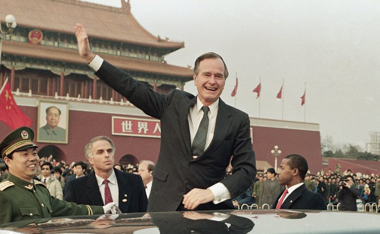 FILE - In this Feb. 25, 1989, file photo, then U.S. President  George H.W. Bush stands on his car and waves to crowds in Tiananman Square in Beijing. Chinese state media are praising Bush as a 'statesman of vision,' recalling the late president's role in helping end the Cold War and establishing policies toward China. AP