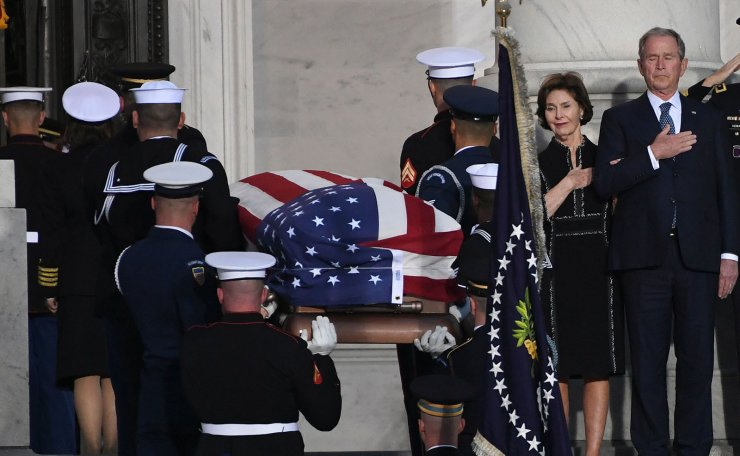 The casket bearing the remains of former US President George H.W. Bush arrives at the US Capitol as former US President George W. Bush (RC) and former First Lady Laura Bush (2R) look on in Washington, DC, December 3, 2018. AFP