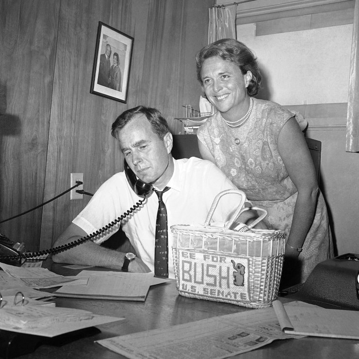 FILE - In this June 6, 1964, file photo George H.W. Bush, candidate for the Republican nomination for the U.S. Senate, gets returns by phone at his headquarters in Houston, as his wife Barbara, smiles at the news. AP