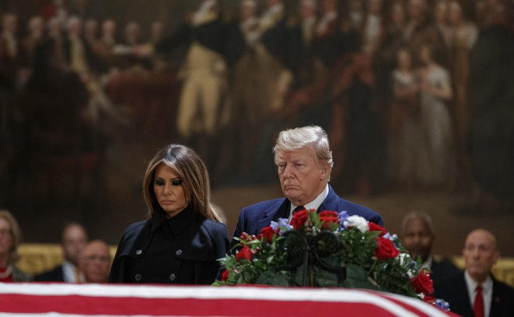 President Donald Trump and first lady Melania Trump have a moment of silence at the flag-draped casket of former President George H.W. Bush in the Rotunda of the Capitol in Washington, Monday, Dec. 3 2018. AP