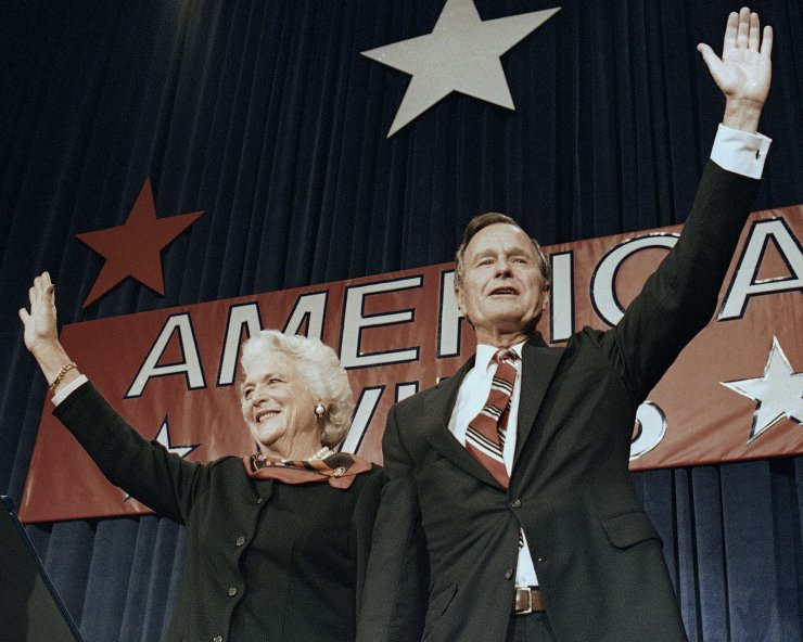 FILE - In this Nov. 8, 1988 file photo, President-elect George H.W. Bush and his wife Barbara wave to supporters in Houston, Texas after winning the presidential election. AP